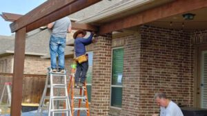 Landscape Construction Workers Attaching Pergola to House
