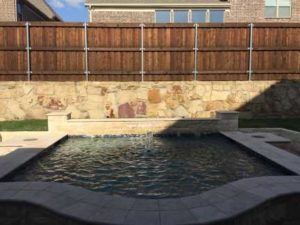 Simple Pool Landscaping, image of design before plant installation with boulder stone retaining wall and chopped stone decorative wall.
